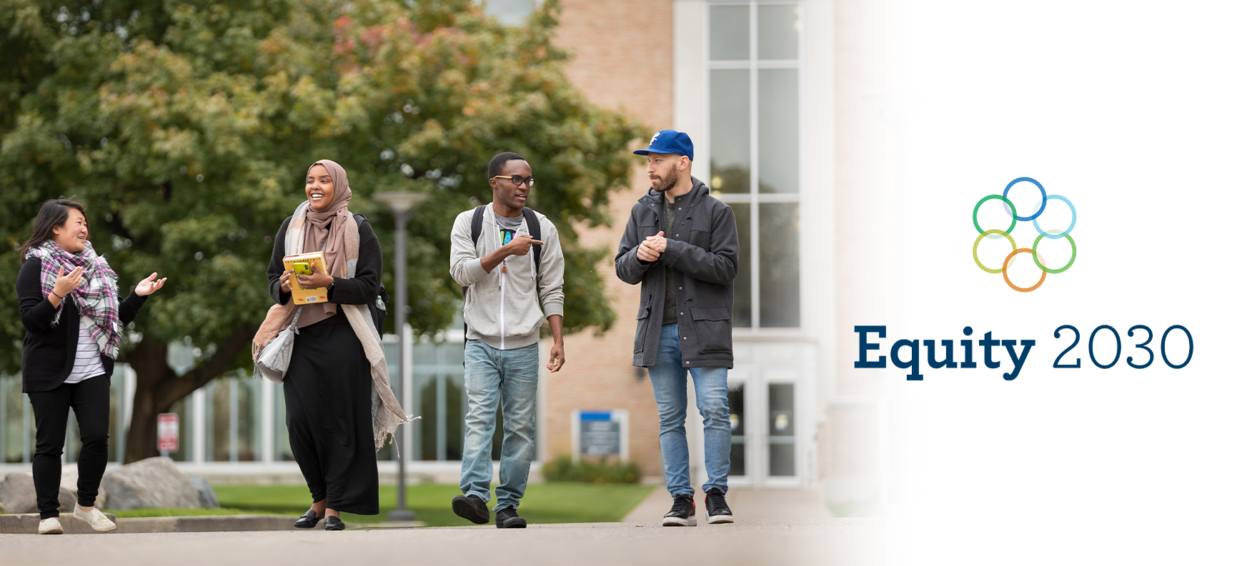 Four students walking together outside on campus