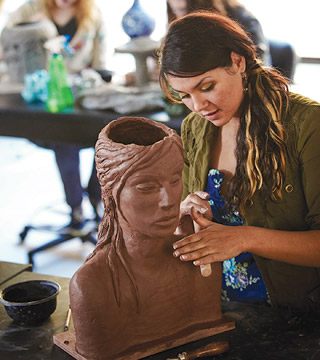 Art student making a clay sculpture.