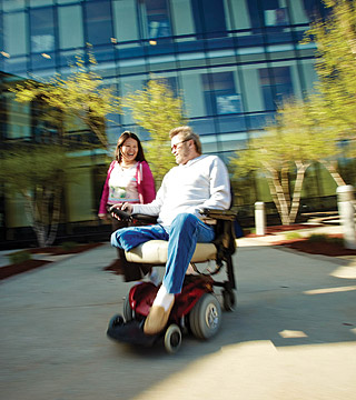 Student in wheelchair in quad area with another student.