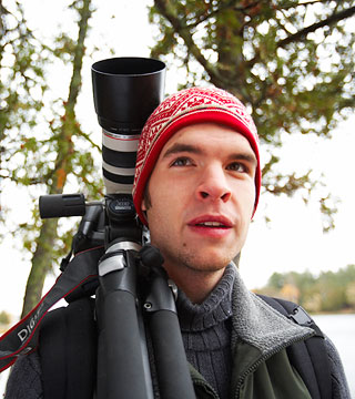 Photography student standing outdoors with camera