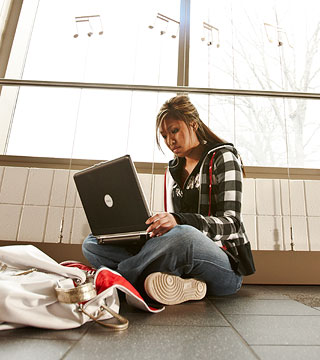 Female student working on laptop in hallway.
