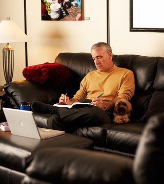 man on couch with a computer